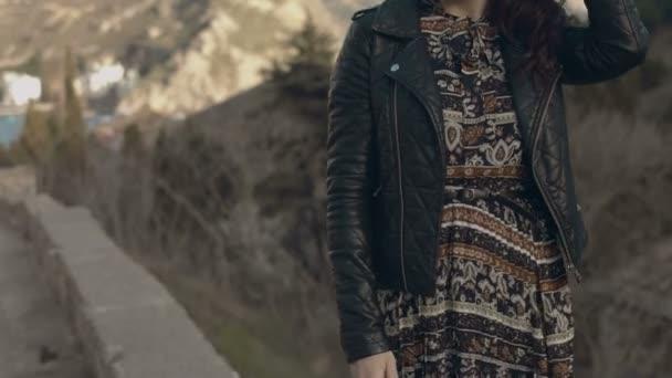 Krásná dívka v šaty a kožené bundě, představují zároveň stojí na parapetu