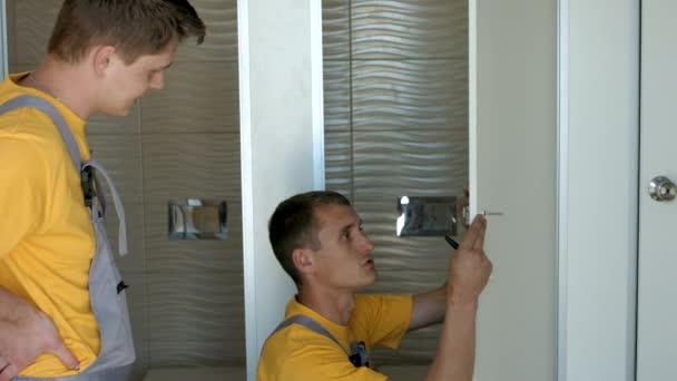 Dělníci jsou instalace zamykání západku na bílé dveře