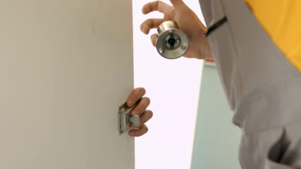 Master přikládá kliku na bílé dveře