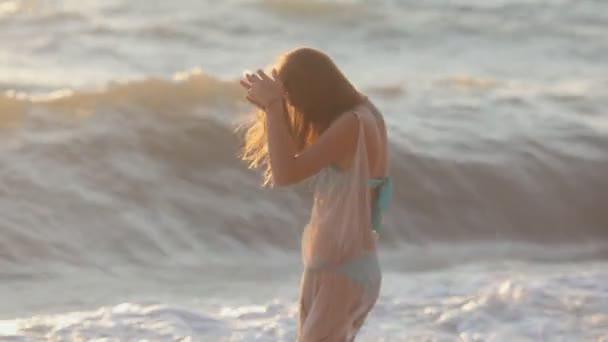 Happy girl runs along the beach and enjoys