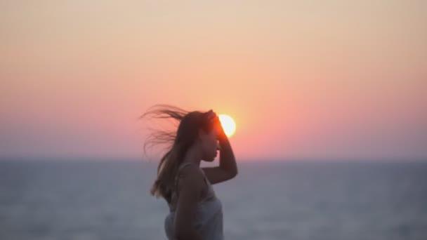Smutný šťastná dívka při pohledu na západ slunce na kopci