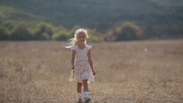 Přemýšlivý holčička jde na louce v pomalém pohybu