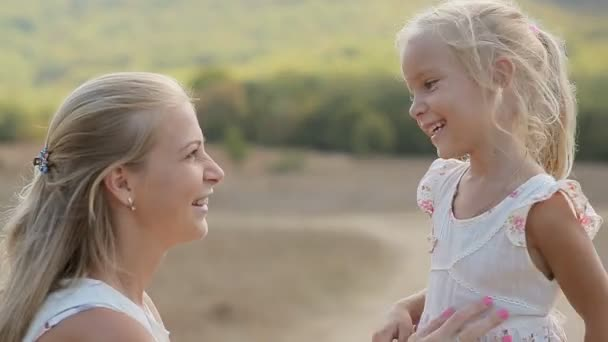Beautiful mother with little daughter laugh and rejoice in the field
