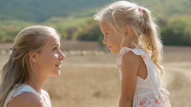 Close up of mother and little daughter embracing and laughing in the middle of the field in slow motion