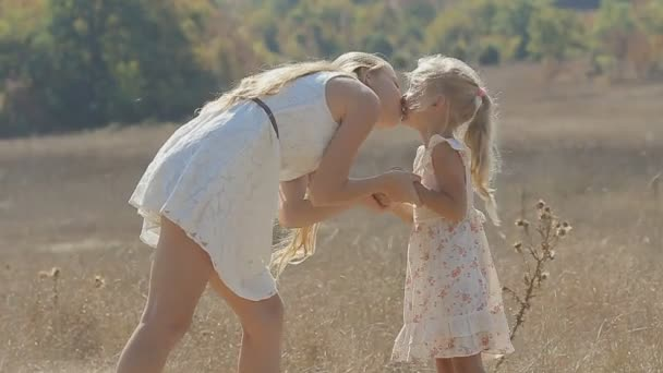 Mami, líbání, objímání a směje se svou malou dcerou v poli v pomalém pohybu