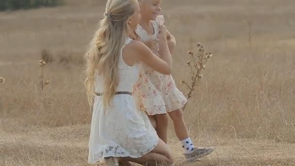 Mamma diverte la sua piccola figlia, abbracciare e baciare lei