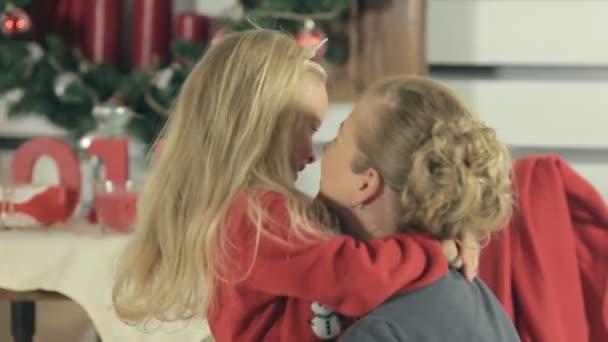 Roztomilá holčička v červený svetr, směje se a baví se s mámou