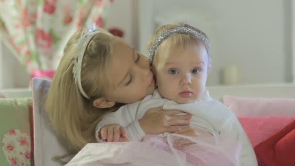 Krásná holčička, sedící na gauči s její mladší sestrou