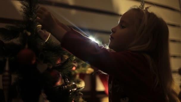 Blonďatá holčička s dlouhými vlasy zdobí vánoční strom se svou matkou v temnotách