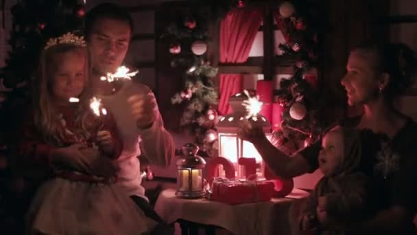 Happy family consisting of parents,  little girl and a baby in a suit of deer sitting at the table and lit sparklers