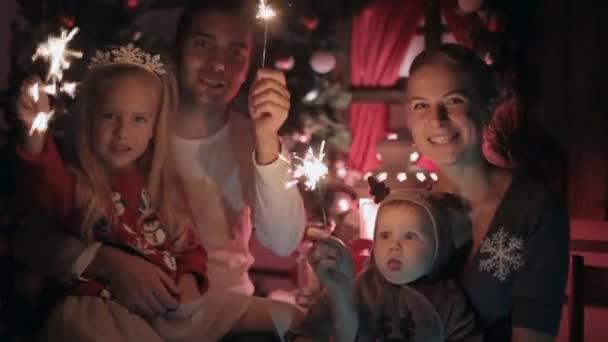 Schöne, glückliche Familie mit zwei Kindern erfüllen Neujahr mit brennenden Wunderkerzen, lachen und Küsse