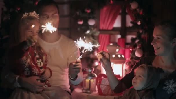 Happy family with young kids lighting sparklers in the dark, kissing and feeling happy
