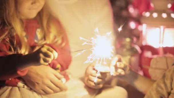 Entzückende Familie leuchtet bengalische Feuer, Lieder singen und feiern das neue Jahr glücklich