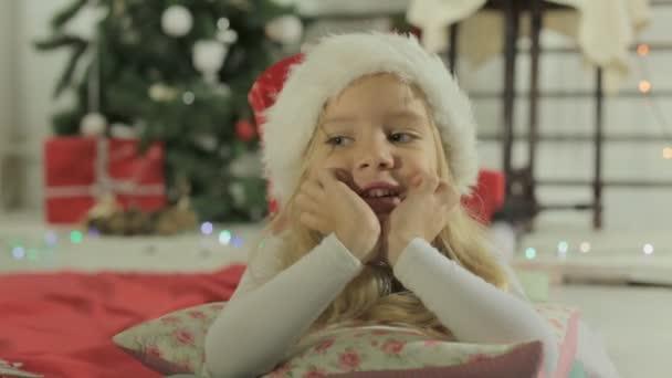 Roztomilá holčička v Santa hat ležela na polštáři u vánočního stromu