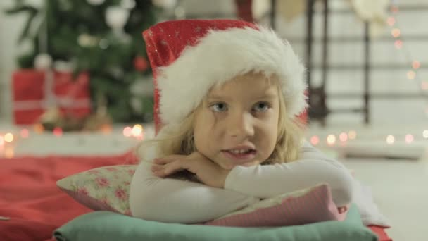 charmantes kleines Mädchen mit Weihnachtsmütze, das auf dem Kopfkissen neben dem Weihnachtsbaum liegt