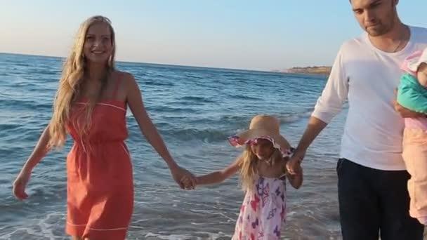 Friendly family walking along the coast in slow motion