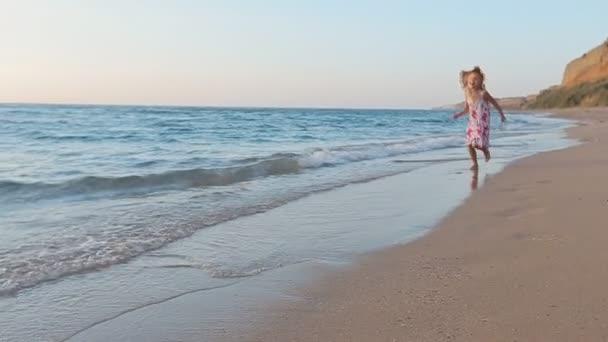 Kislány fut a tenger mentén, apja lábnyomokat hagyva a homokban, és ő felemeli őt megjelöl-a lassú mozgás