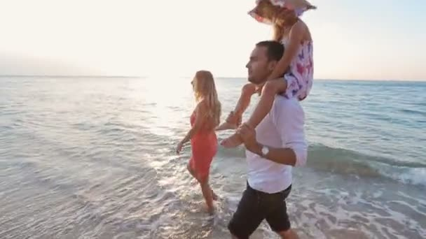 Šťastná rodina, procházky po pláži naboso