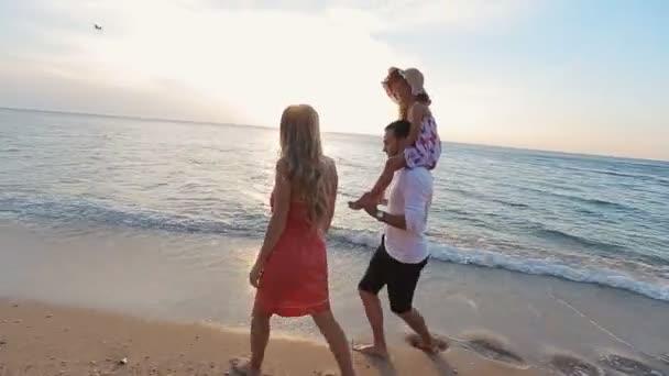 Přátelské rodinné procházky podél pláže a ponechává stopy v písku