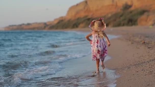Malá holčička runing podél pláže v letní šaty v zpomalený pohled zezadu