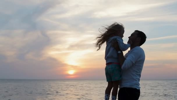Father throws up in the air little happy girl near the sea in slow motion