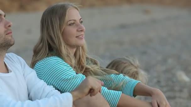 Zblízka šťastná rodina s malou dcerou sedí u moře a hází kameny do vody