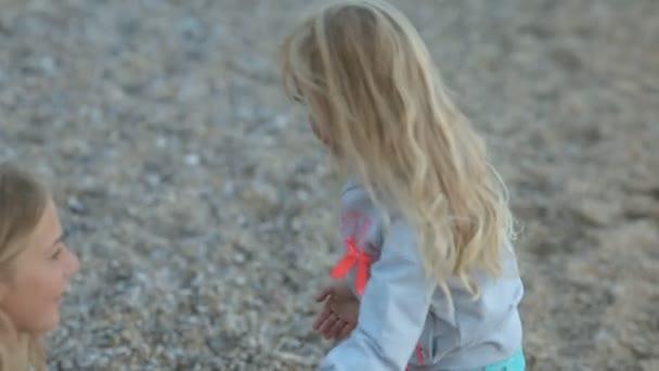 Malá holčička se svými rodiči v blízkosti moře