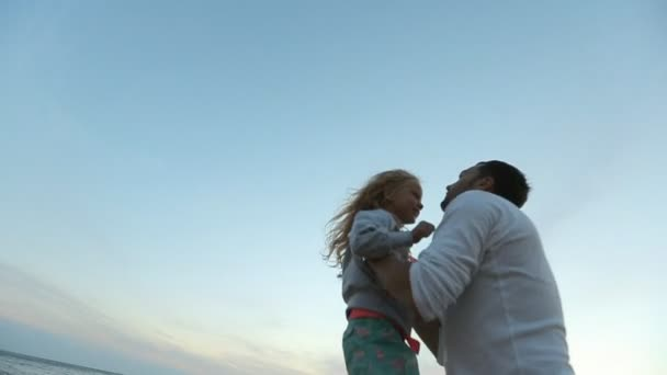 Father takes daughter in his arms and throws up into the air in slow motion