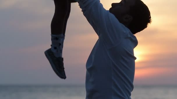 Close up of father throwing up his daughter in the air at sunset in slow motion