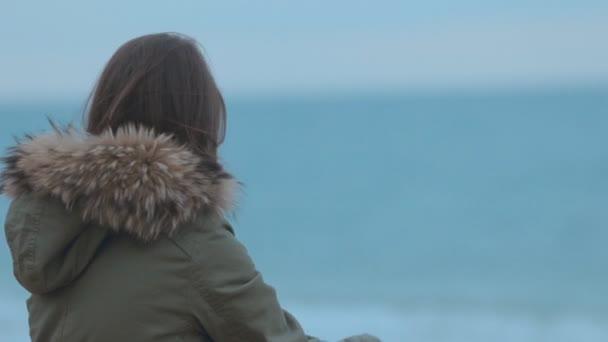 Dívka sedí u moře a hází kameny ve vodě