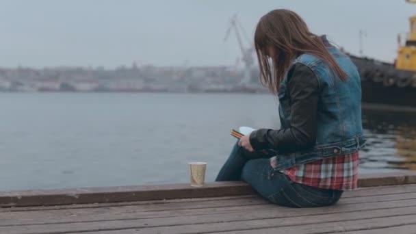 Vstřebává v kreslení dívku sedící na dřevěném molu u moře