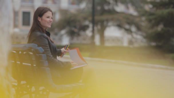 Talentovaný brunetka kreslení v albu s světlé tužky sedí na lavičce v parku n