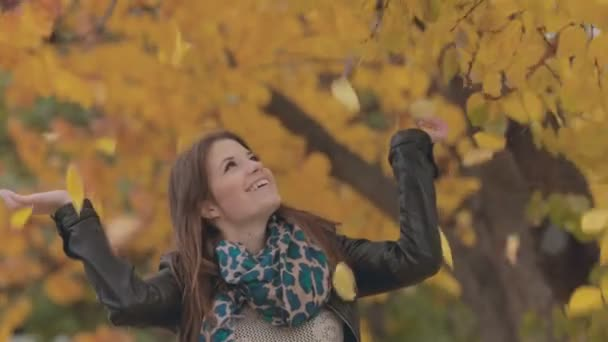 Lovely girl laughing under a tree from where yellow leaves falling