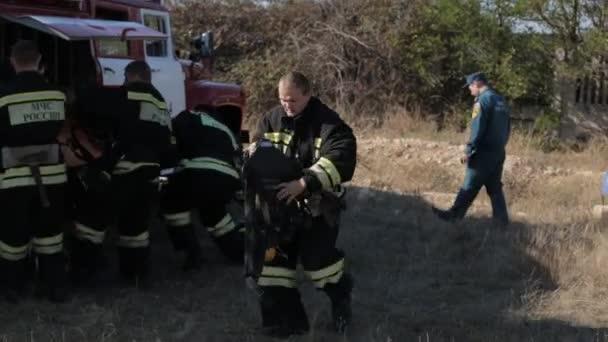 Hasiči nosí uniformy poblíž hasičský vůz a spusťte uhasit požár