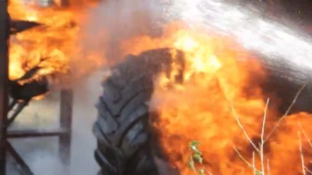 Hasič hasí oheň pomocí vody