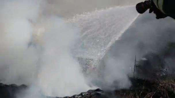 Hasič hasí oheň s proudem vody z hadice