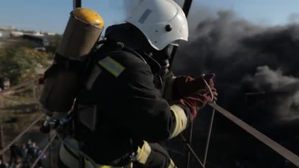 Hasiči sobě plynové masky dělat svou práci v kouři ve vysoké nadmořské výšce