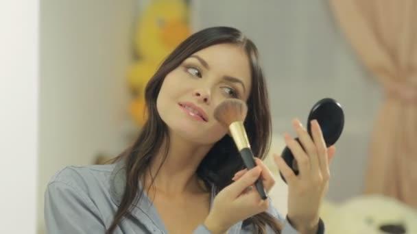 Atraktivní brunetka prášky její tvář s kartáčem a při pohledu do zrcadla