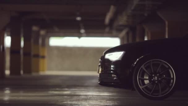Černé Audi opustí parkoviště s rozsvícenými světly na