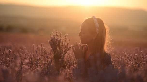 Beautiful girl is sitting in the middle of a field of blossoming lavender with a bouquet at sunset
