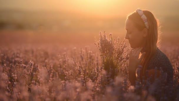 Šťastný a pohodovou dívku sedící uprostřed pole kvetoucí levandule s kyticí při západu slunce