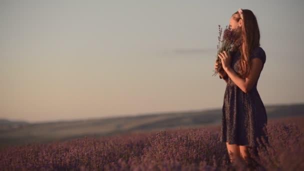 Romantická dívka stojící uprostřed kvetoucí levandule a čichání kytice levandule