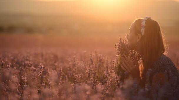 Šťastný a pohodovou dívku sedící uprostřed pole kvetoucí levandule a čichání kytice levandule při západu slunce