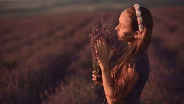Zasněný dívka v letní šaty, stojící uprostřed kvetoucí pole levandule s vůní levandule