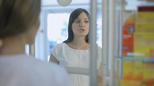 Young pregnant woman talking to pharmacist in a drugstore