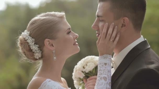 Krásná nevěsta a ženich, líbání a mazlení na povaze