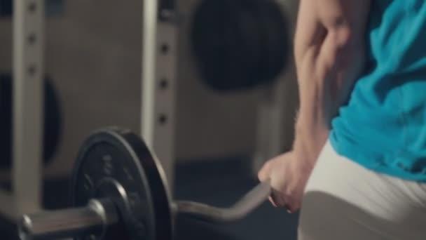 Svalnatý muž zvedne činka z podlahy a budovat svaly