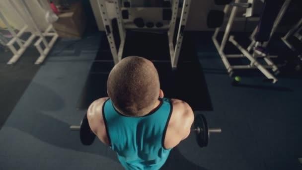 Svalnatý muž dělá cvičení pro biceps s činka v tělocvičně
