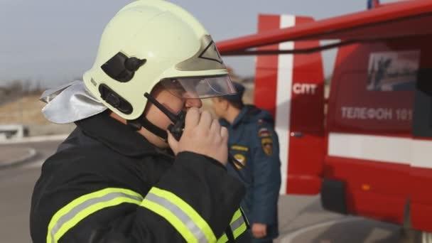 Sevastopol, Krym, Rusko - 26 března 2015: Cvičení hasičů. Hasič rozhovory od rádia, hasiči příprava na cvičení