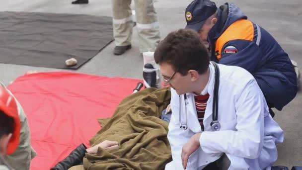 Sevastopol, Krym, Rusko - 26 března 2015: Cvičení hasičů. Lékaři a zachránci poskytnout první pomoc člověka, který byl evakuován. Dejte mu kyslíkovou masku